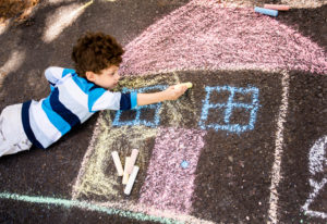 Child drawing house chalk on street